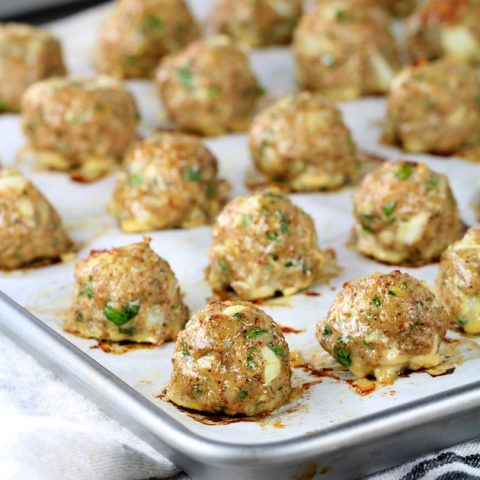 Baking sheet with cooked meatballs on parchment