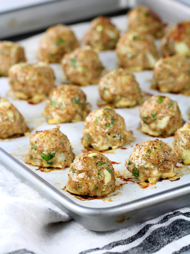 Eye level partial baking sheet of cooked turkey meatballs