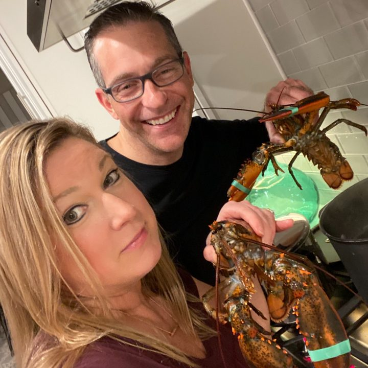 2 people holding live lobsters over pot