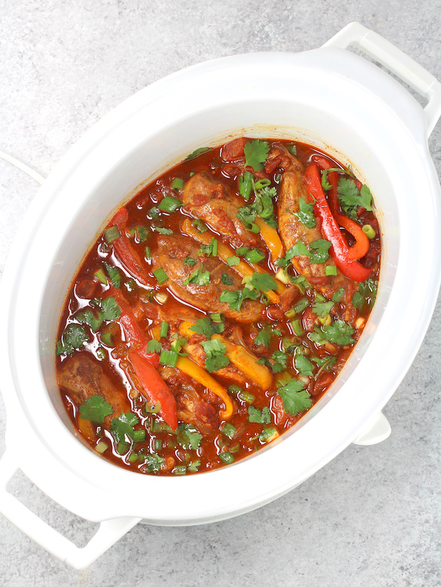 slow cooker full of Mexican chicken, peppers and onions with cilantro
