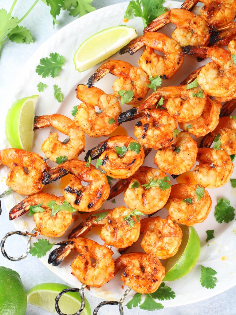 grilled gulf shrimp skewers on platter with lime wedges