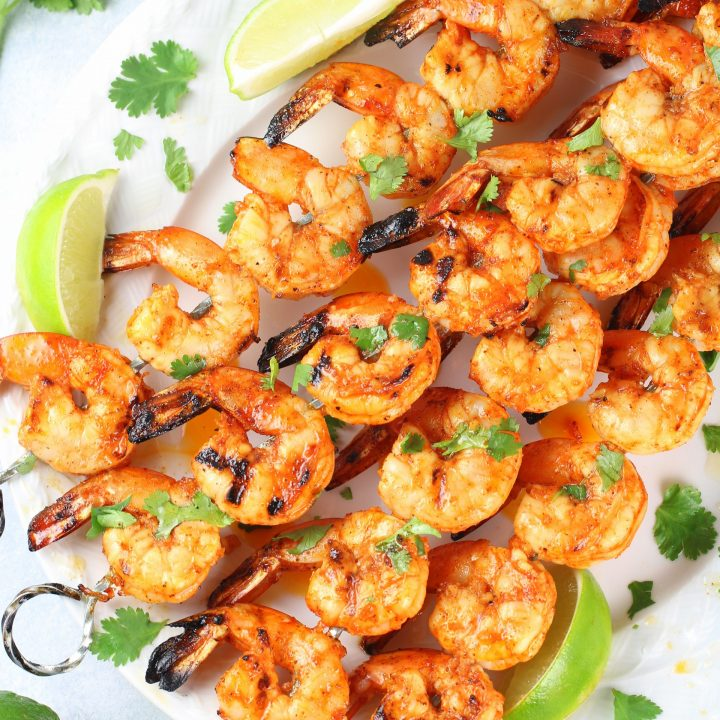 skewers of grilled gulf shrimp on platter with limes