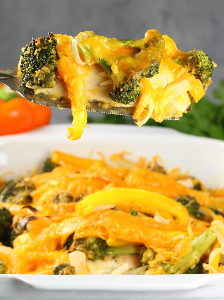 Spatula holding Chicken Casserole with bell peppers, broccoli, and cheese
